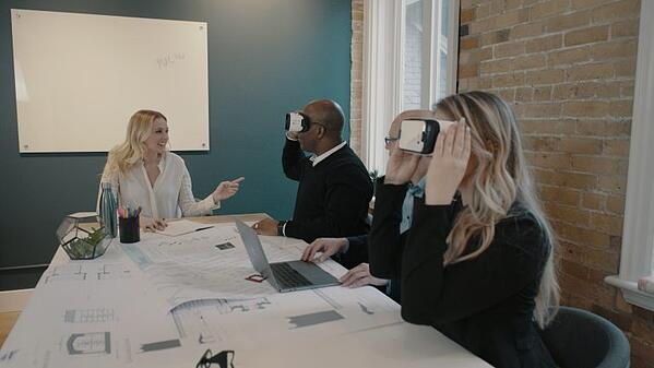 People sitting around a table using VR headsets