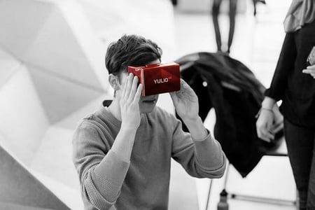 Man holding cardboard Yulio branded headset