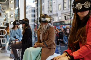 VR for Retail experience at topshop where 4 young women sitting in front of a large store window are wearing VR headsets.