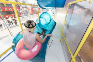 A young woman with blonde hair and a pink shirt sits in an inflatable pool toy at the top of a tube shaped waterslide in a store.