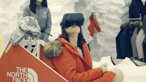 A woman sits in a reconstruction of a dog sled wearing a red coat and VR headset. She's using VR for retail in a North Face outdoor store.