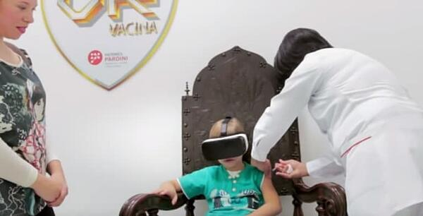 Child getting injection and wearing a VR headset