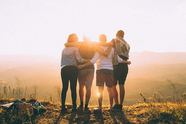 friends hugging and looking at the sunset