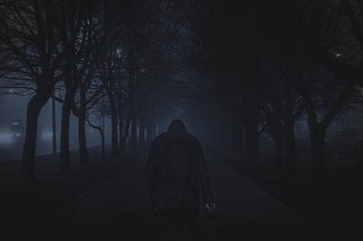 Man walking between trees at night.